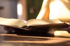 Vrouw die een boek, hard licht lezen stock foto