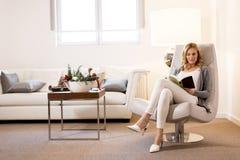 Vrouw die een boek lezen en op comfortabele stoel thuis zitten royalty-vrije stock foto