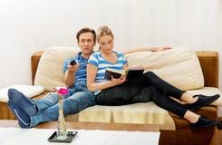 Vrouw die een boek lezen terwijl haar echtgenoot op TV in woonkamer let Stock Foto
