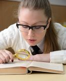 Vrouw die een boek met een vergrootglas leest Royalty-vrije Stock Fotografie
