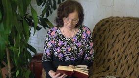 Vrouw die een boek op de laag leest stock videobeelden