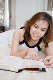 Vrouw die een boek op haar bed lezen Stock Foto