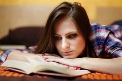Vrouw die een boek op het bed leest Stock Foto