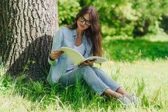 Vrouw die een boek in park lezen Royalty-vrije Stock Foto's