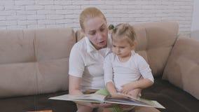 Vrouw die een boek van kinderen voor een kleine meisjeszitting lezen met een kind op de laag stock video