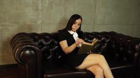 Vrouw die een boekzitting op een leerbank lezen Vrouwelijke lezing in de woonkamer stock footage