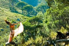Vrouw die in een bos dansen die haar haar met bomen op de achtergrond flicking stock afbeeldingen