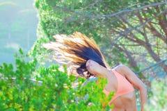 Vrouw die in een bos dansen die haar haar met bomen op de achtergrond flicking royalty-vrije stock afbeeldingen
