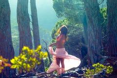 Vrouw die in een bos dansen die haar haar met bomen op de achtergrond flicking stock foto's