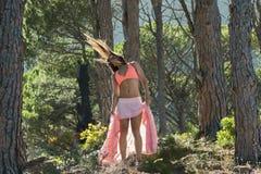 Vrouw die in een bos dansen die haar haar met bomen op de achtergrond flicking royalty-vrije stock fotografie