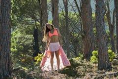 Vrouw die in een bos dansen die haar haar met bomen op de achtergrond flicking stock afbeelding