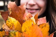 Vrouw die een bos van de herfstbladeren houden Royalty-vrije Stock Fotografie