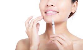 Vrouw die een botoxinjectie in haar lip ontvangt Stock Afbeeldingen