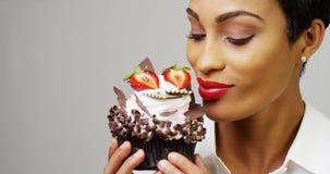 Vrouw die een buitensporig dessert cupcake met chocolade en aardbeien bewonderen Stock Foto's
