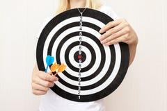 Vrouw die een dartboard en pijltjes in handen tegenhouden die dicht, en in bedrijfs en het levensconcept streven richten royalty-vrije stock afbeeldingen