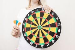 Vrouw die een dartboard en pijltjes in handen tegenhouden die dicht, en in bedrijfs en het levensconcept streven richten royalty-vrije stock foto