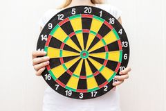 Vrouw die een dartboard in handen tegenhouden dicht, en concept streven richten royalty-vrije stock afbeelding
