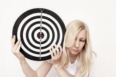 Vrouw die een dartboard in handen tegenhouden dicht, en concept streven richten stock foto