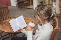 Vrouw die een document boek met een kop van koffie lezen royalty-vrije stock foto's