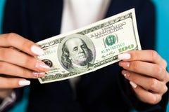 vrouw die een 100 dollarrekening houden Stock Afbeeldingen
