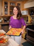 Vrouw die een droger rek van tomaten houden Stock Afbeeldingen