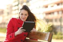 Vrouw die een ebook of een tablet in een stedelijk park lezen stock foto's