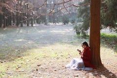 Vrouw die een ebook of een tablet in een stedelijk park lezen, stock afbeeldingen