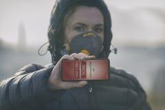 Vrouw die een echt antimistgezichtsmasker dragen en huidige luchtvervuiling met smartphone app controleren stock afbeelding