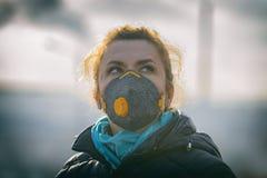 Vrouw die een echt masker van het anti-vervuilings, antimist en virussengezicht dragen stock fotografie