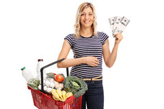 Vrouw die een een het winkelen mand en geld houden Stock Afbeeldingen