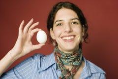 Vrouw die een ei houdt Stock Afbeeldingen