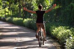 Vrouw die een fiets berijden op zonnige parksleep royalty-vrije stock fotografie