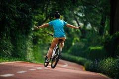 Vrouw die een fiets berijden op zonnige parksleep stock afbeelding