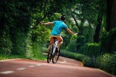 Vrouw die een fiets berijden op zonnige parksleep royalty-vrije stock foto's