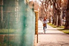 Vrouw die een fiets berijden tijdens de lentedag in de stad Royalty-vrije Stock Fotografie