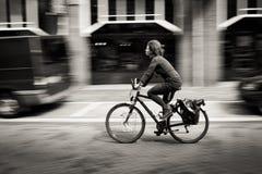Vrouw die een fiets onderaan de straat berijden. Amsterdam Royalty-vrije Stock Afbeeldingen