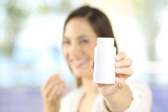 Vrouw die een fles van pillen tonen Stock Afbeeldingen