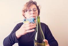 Vrouw die een fles van wijn met een ecologische streng verfraaien Rustieke stijl, met de hand gemaakte ambacht Gift voor Kerstmis royalty-vrije stock afbeeldingen