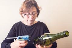 Vrouw die een fles van wijn met een ecologische streng verfraaien Rustieke stijl, met de hand gemaakte ambacht Gift voor Kerstmis stock foto's