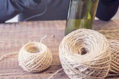Vrouw die een fles van wijn met een ecologische streng verfraaien Rustieke stijl, met de hand gemaakte ambacht Gift voor Kerstmis stock foto