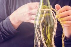 Vrouw die een fles van wijn met een ecologische streng verfraaien Rustieke stijl, met de hand gemaakte ambacht Gift voor Kerstmis royalty-vrije stock fotografie