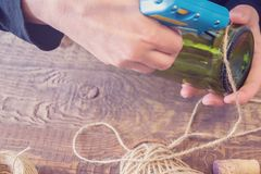 Vrouw die een fles van wijn met een ecologische streng verfraaien Rustieke stijl, met de hand gemaakte ambacht Gift voor Kerstmis stock afbeelding