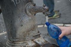 Vrouw die een fles vullen met drinkbaar water in een openbare fontein van Rome stock fotografie