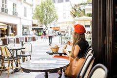 Vrouw die een Frans ontbijt hebben bij de koffie stock afbeeldingen