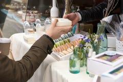Vrouw die een Franse macaron kopen stock foto