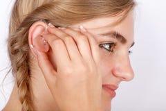 Vrouw die een gehoorapparaat opnemen in oor Royalty-vrije Stock Foto