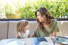 Vrouw die een gelukkig verhaal vertellen aan meisje in restaurant stock fotografie