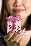 Vrouw die een gift houdt Stock Foto's