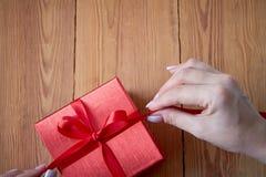 Vrouw die een giftdoos in een gebaar van het geven houden royalty-vrije stock afbeeldingen