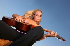 Vrouw die een gitaar speelt Royalty-vrije Stock Afbeelding